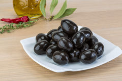 Black olives. In the bowl on wood background royalty free stock photo