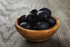 Black olives from can in bowl on table Royalty Free Stock Images