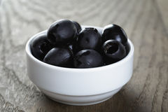 Black olives from can in bowl on table Stock Photo