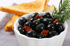 Black olives with dried tomatoes and toasts Royalty Free Stock Images