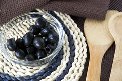 Black olives in glass bowl with wooden spoon Royalty Free Stock Image