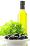 Black olives, greens and oil Stock Images