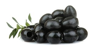 Black olives in a heap with leaves close up on a white isolated background royalty free stock photo