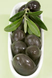 Black olives with leaves Royalty Free Stock Images
