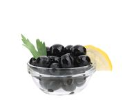 Black olives with lemon in bowl. Royalty Free Stock Images