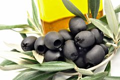 Black olives with oil bottle. Some black olives together with other oil bottle to the bottom Stock Photography