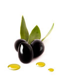 Black olives with oil drops on white Stock Images