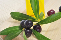 Black olives and olive oil. Closeup of a bunch of black olives and a bottle of olive oil Royalty Free Stock Photography