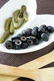 Black olives and pickles with wooden spoon Stock Photography