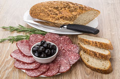 Black olives and pieces of sausage, bread, rosemary and knife Royalty Free Stock Image