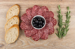 Black olives and pieces of smoked sausage, bread and rosemary Royalty Free Stock Images