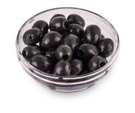 Black Olives without pits lie in a glass cup on  the white  back. Ground Stock Images