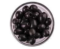 Black Olives without pits lie in a glass cup on  the white  back. Ground Royalty Free Stock Images