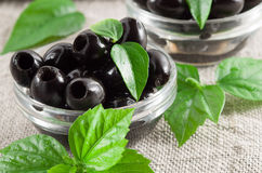 Black olives, pitted marinated in a glass bowl Royalty Free Stock Photos