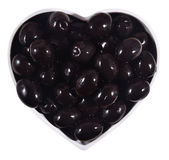 Black olives in plate in the form of heart on a white Royalty Free Stock Photography