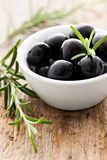 Black olives. With rosemary in a bowl stock images
