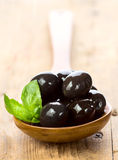 Black olives in a spoon on wooden table Royalty Free Stock Images