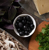 Black olives surrounded by products. Black olives surrounded by other products Royalty Free Stock Photos
