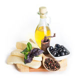 Black olives in white bowl, olive oil and cheese Stock Photo