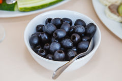 Black Olives. Black Olives in a white Cup on the table. The dish on the table. Serving in the restaurant. Food. Fruits and vegetables. Breakfast, lunch, dinner Royalty Free Stock Photo