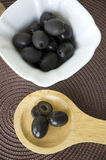Black olives in wooden spoon Stock Photo