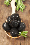 Black olives in a wooden spoon close-up Stock Photo
