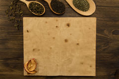 Black, Oolong in a spoon, dried apples on the old blank open book on wooden background. Royalty Free Stock Image
