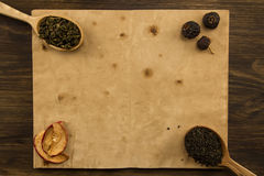 Black, Oolong in a spoon, dried apples on the old blank open book on wooden background. Menu, recipe Stock Images