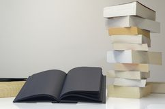 Black open book in foreground of pile of books. On the white table and light grey background royalty free stock images