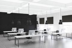 Black open space office corner, rows of desks Royalty Free Stock Image