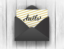 Black opened envelope with Hello Lettering on wooden background. Stock Images
