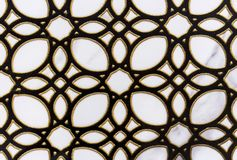 Black openwork ornament with a gold border on a white ceramic tile stock photography