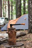 Black orange axe in the wooden stump on the background of tent a stock photo