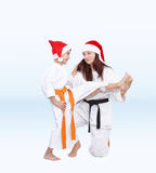 With black and orange belt in caps of Santa Claus sport family are training kick leg Stock Photo