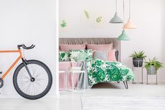 Black and orange bike. Standing in white bedroom with floral bedsheets Stock Photo