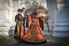 Black and orange costumed masked couple. At San Zaccaria in Venice Royalty Free Stock Photo