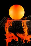 Black and orange liquid art. A view of an orange ball sitting on top of a vase, which is filled with transparent liquid. Orange ink in the liquid is dissolving stock photo