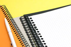 Black and orange notepads, sheet of paper with pen on yellow wri Stock Photo