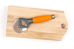 Black and orange round pizza knife on the cutting wooden board Royalty Free Stock Photo