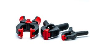 Black and orange spring clamp isolated on white background. Set of small, medium, and big size of plastic clamp. Clamping tools royalty free stock photography