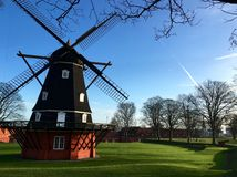 Black and Orange Windmill Surrounded by Green Grasses Royalty Free Stock Images
