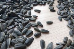 Black organic sunflower seeds on wooden background royalty free stock photo
