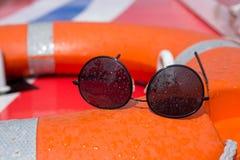 5a50e32b7a5 Black oval sunglasses on board a boat covered in sea spray stock photos