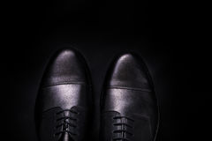 Black oxford shoes on  background. Top view. Copy space. Black oxford shoes on black background. Top view. Copy space Royalty Free Stock Images