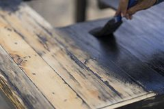 Black paint with brush on wood. stock photos