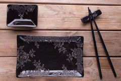 Black painted chopsticks and empty square plate Royalty Free Stock Photos
