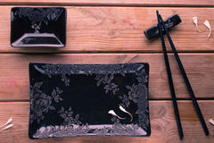 Black painted chopsticks and empty square plate Royalty Free Stock Photography