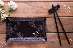 Black painted chopsticks and empty square plate Royalty Free Stock Photo