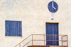Black painted door window and clock. Door and window covered with black painted planks on old beige industrial building. Clock on wall is fake made of black Stock Images