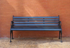 Black painted timber bench with brick wall background Royalty Free Stock Photo